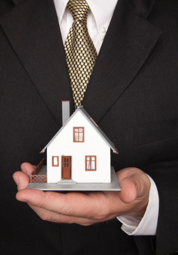 Top 10 tips to prepare your finances for a home loan (Man in suit holding house)