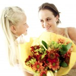 Girl (6-8) Giving a Bouquet of Flowers to a Young Woman